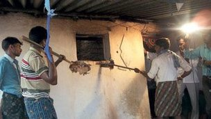 Officials use sticks to break into the room where Keshava had been confined for more than a decade