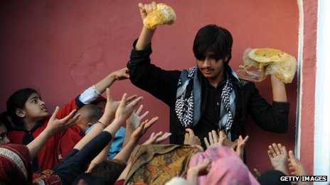 A Pakistani man distributes food to Muslim devotees at the shrine of the Sufi saint Mian Mir Sahib in Lahore in 2011