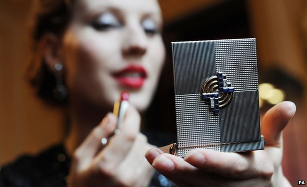 Woman applying lipstick in the mirror of a Gatsby-style make-up box