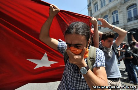 Protestors hold a giant Turkish flag in front of a water cannon truck (31 May 2013)