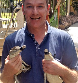 Phil Mercer holding two baby crocodiles