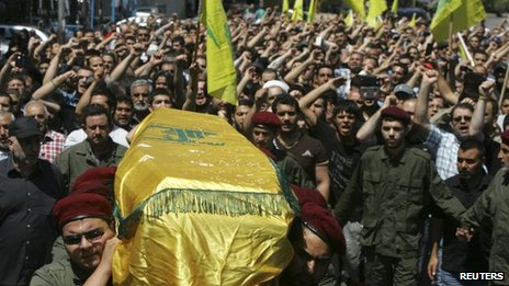 Hezbollah supporters carry the coffin of a militant killed fighting in Syria through the streets of Beirut (21 May 2013)