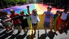 Gay rights supporters march with a rainbow flag during the gay pride parade in Salt Lake City, Utah