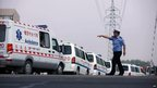 A police officer directs an ambulance outside Baoyuan poultry plant at Dehui, in north-east China's Jilin province, following a factory fire, 3 June 2013