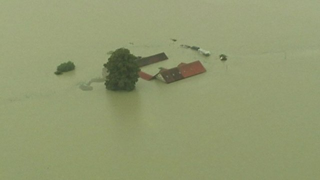 A house submerged in water as far as its roof