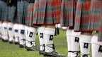 A row of men wearing kilts
