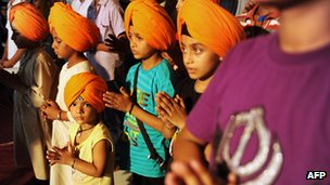 Indian Sikh members praying after a turban-tying ceremony known as 'dastar bandi', traditionally held to mark the coming of age of male Sikhs, at a temple in Amritsar 7 July 2012