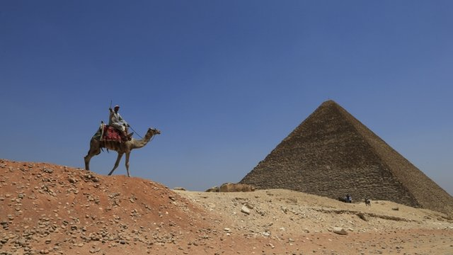 A man rides a camel past a pyramid at Giza