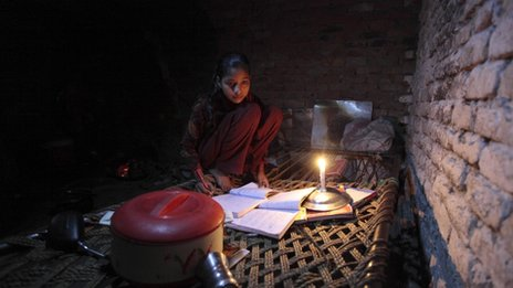 Noreen, 13, uses candlelight as she studies during a power cut in a slum in Islamaba