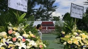 A man walks past wreaths and a backdrop showing Tiananmen Square in June 1989 at Hong Kong's Victoria Park 4 June  2013