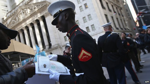 US Marine Lance Cpl Torffic Hassan from Ghana looks over his citizenship certificate on Wall Street on 22 March 2013