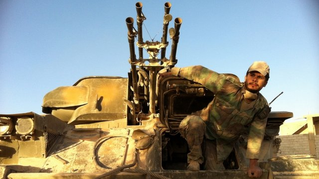 A Syrian army soldier exits his tank