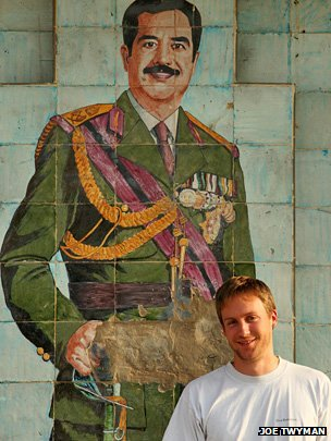 Joe Twyman in front of a mural of Saddam Hussein