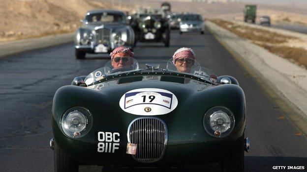 A couple in Arab head-dresses drive a C-type Jaguar near Kerak, Jordan