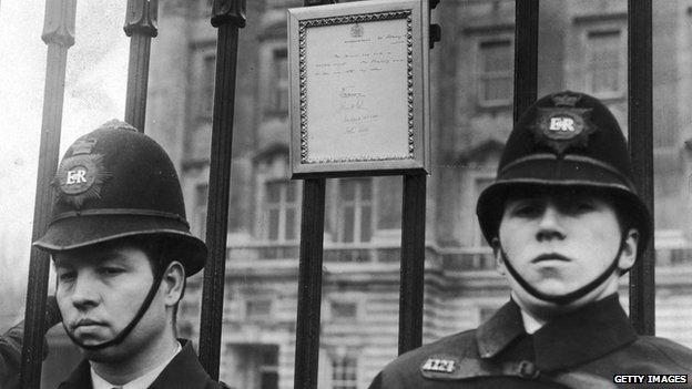 Two policeman standing either side of a royal bulletin announcing the birth of the Queen's new son, Edward, at Buckingham Palace, London in 1965