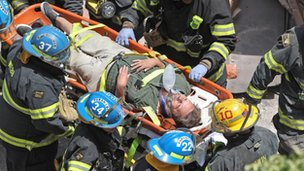 Firefighters carry a survivor from the rubble of a building collapse in downtown Philadelphia 5 June 2013