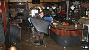 Helpers clean a flooded bar in the city of Passau in Germany