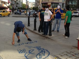 Protesters draw a graffito of PM Erdogan