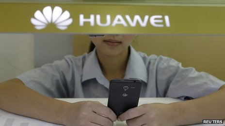 Sales assistant looks at a smartphone in Huawei store