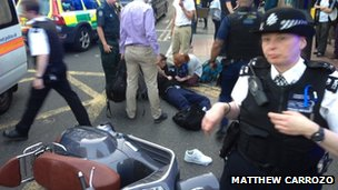 Police, medics and passers-by around a man who came off a moped