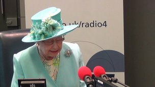 The Queen speaks into a microphone