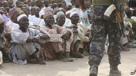 People watch as a soldier walks by before a meeting with military commanders in the village of Kerinowa, Nigeria - Wednesday 5 June 2013