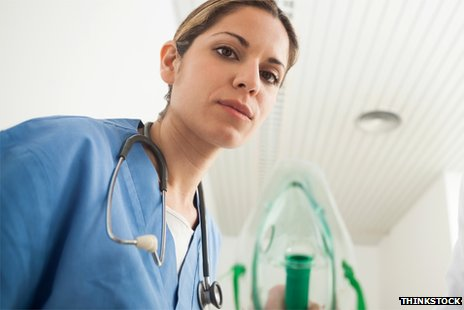 Generic image of a nurse leaning towards the camera, as though over a patient