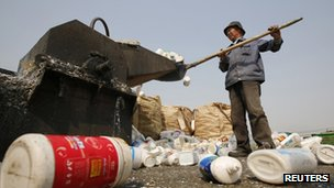 A worker shovels plastic bottles into a shredder at a recycling depot in Beijing 26 April 2013