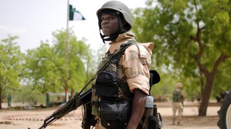 Nigerian soldier part of the joint forces in Borno state near a Nigerian flag at the Maiduguri Nigerian military headquarters in Maiduguri on 5 June 2013