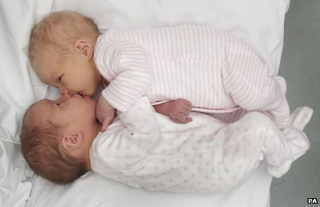 New-born Rodger twins lying face to face in a bed