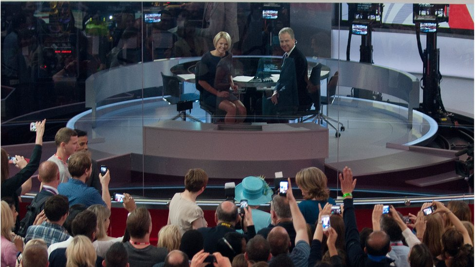 The Queen appears on the BBC News Channel behind the newsreaders