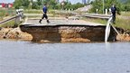 Emergency services workers inspect a road washed away by flood water near Loebnitz, eastern Germany, 7 June 2013
