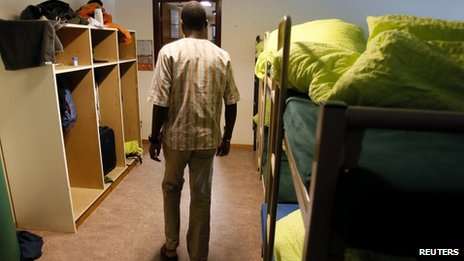 "An asylum seeker walks past beds in a sleeping room of the asylum centre ""Les Pradieres"" for refugees during a tour for media in Val-de-Ruz near Neuchatel"