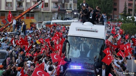 Supporters of Prime Minister Erdogan gather around his convoy waving flags