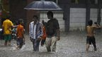 Children play as two men walk through a flooded street during monsoon rains in Mumbai, India, Sunday, June 9, 2013. The Southwest monsoon, arrived in the city Saturday, three days ahead of schedule, according to the meteorological department