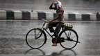 An Indian man on bicycle protects himself with a plastic bag from a heavy monsoon shower in Hyderabad, India, Saturday, June 8, 2013.