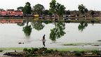 Indian children wade through a submerged area after a rain shower in Allahabad on June 9, 2013