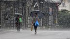 People hold umbrellas as they walk in a heavy rain shower in the northern Indian hill town of Shimla June 6, 2013. I