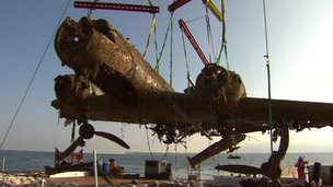 The wreckage of a plane being lifted out of the sea