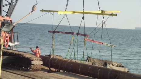Crane operators pulling the rusted plane out of the sea