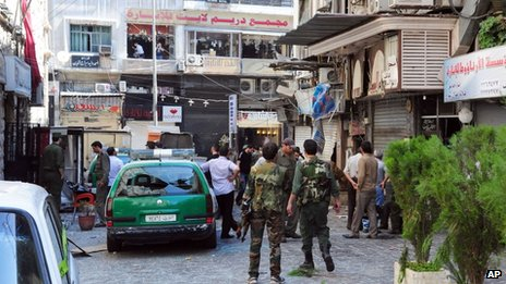 Syrian army soldiers stand guard at a scene of two explosions in the central district of Marjeh, Damascus, Syria ( Image provided by Syrian news agency SANA)