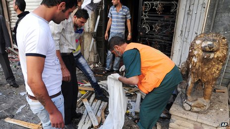 Syrians inspect damaged shops at a scene of two explosions in the central district of Marjeh, Damascus, Syria (s photo released by the Syrian official news agency SANA)