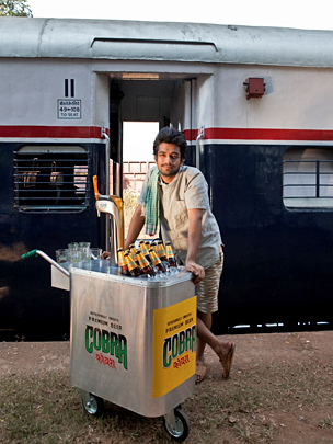 Image from Cobra advert set aboard an Indian train, showing a beer vendor pushing through the aisles
