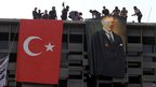 Police hang a banner of Mustafa Kemal Ataturk, founder of modern Turkey, next to a Turkish flag on a building overlooking Taksim Square, Istanbul, on 11 June 2013