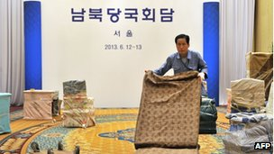 "A South Korean worker removes office fixtures at the venue for the inter-Korean talks after their cancellation at a hotel in Seoul on 12 June 2013. The Korean letters read ""South and North Korean Governments Meeting"""