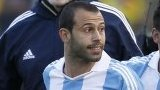 Argentina's Javier Mascherano is held by team-mate Ezequiel Lavezzi