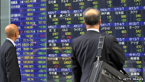 Businessmen look at a share prices board on a window of a securities firm in Tokyo