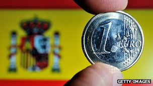 A euro coin being held up in front of a Spanish flag