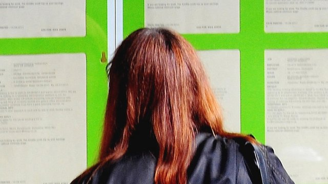 Woman looking into the window of a Job Centre