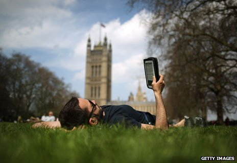 Man reading e-reader near parliament